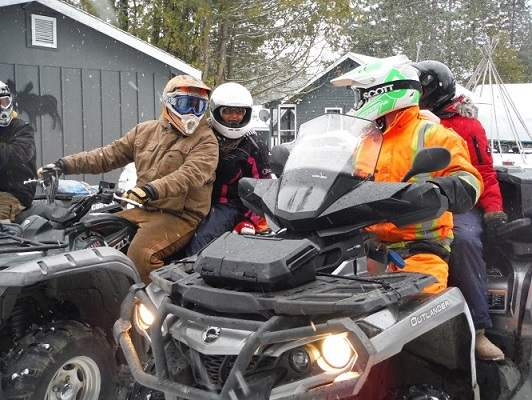 image of four ATV riders near cottage