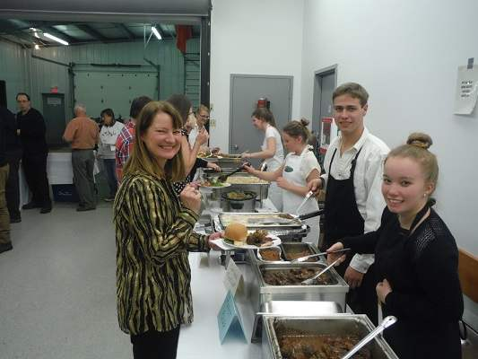 photo of Cindy and other staff helping to serve at Wild Game Dinner