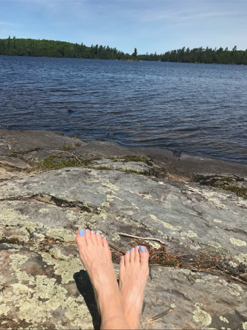 photo of woman's feet in foreground and view of rocks and lake