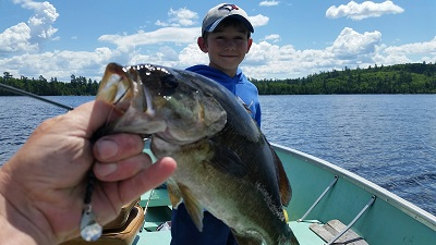photo of smiling young boy in boat, with close up of large bass he caught