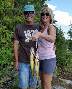 photo of couple on shore with two big fish