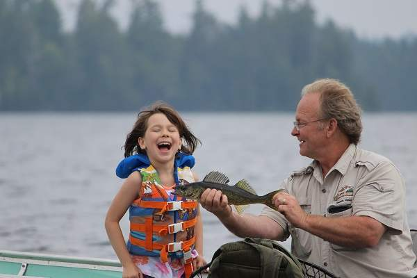 photo of man showing little girl a fish in boat