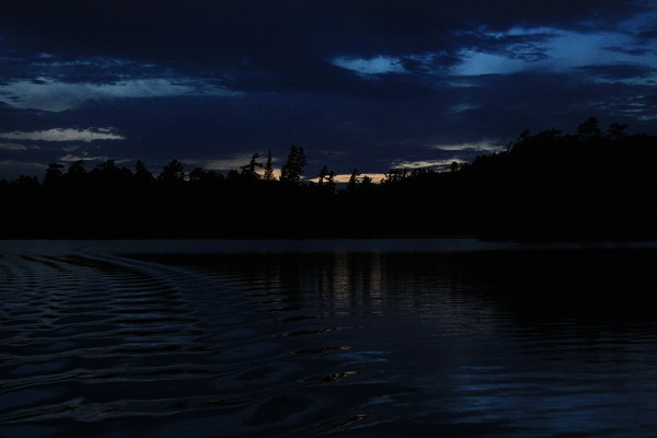 photo of boat's wake in lake at deep twilight