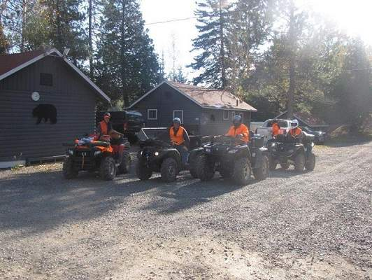 photo of four men in hunting vests on ATVs