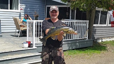 photo of man holding very large pickerel in front of lodge