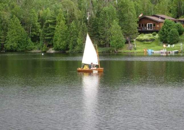 image of small wooden boat with white sail on lake