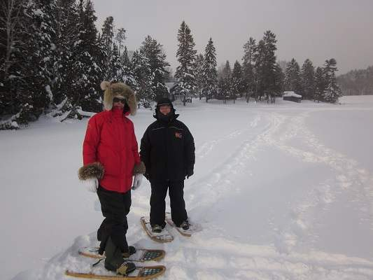 photo of two women snowshoeing on lake