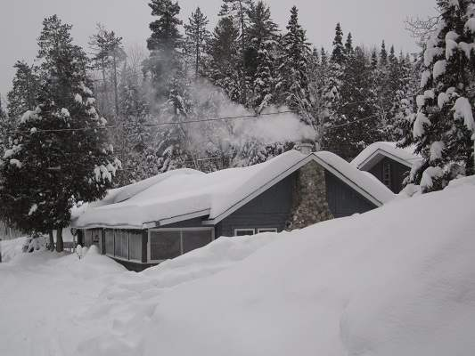 photo of snow-covered guest lodge with smoking chimney