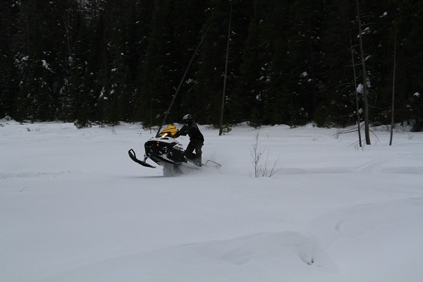 photo of snowmobile rider doing a flying leap on a frozen lake