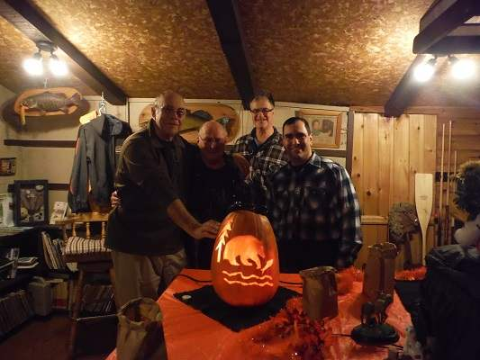 image of four men in guest lodge with jack-o-lantern