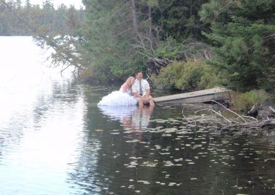 image of a bride and groom on sitting on a dock, legs in water