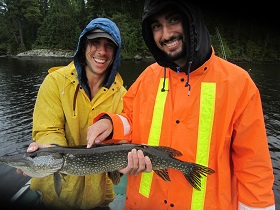 photo of two young men in boat with very large northern pike
