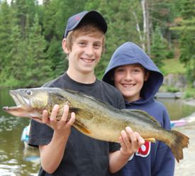 photo of two kids on shore with big pike
