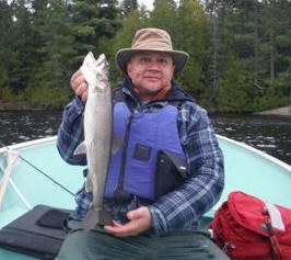 photo of man in boat with large whitefish