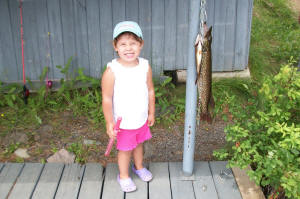 photo of little girl with large northern pike she caught on pink toy fishing pole