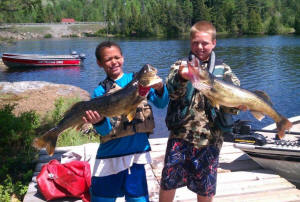 photo of two boys on dock with very large lake trout