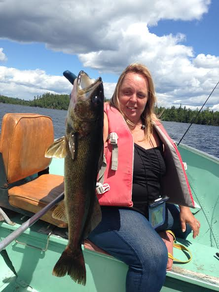 photo of smiling woman in boat, holding very large pickerel