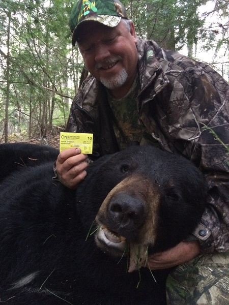 photo of man with large harvested bear