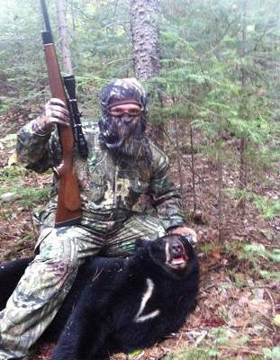photo of man in camoflage with harvested bear