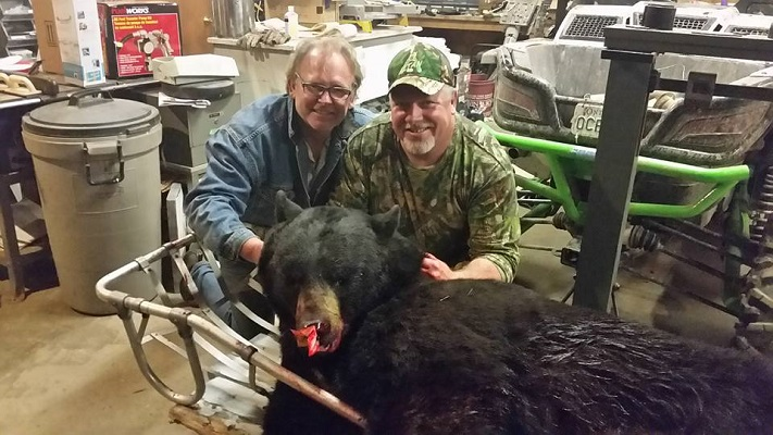photo of Dan and a hunter with a huge harvested bear