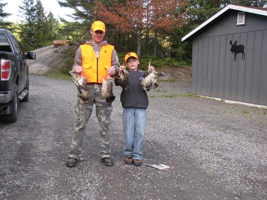 photo of father and son with harvested grouse